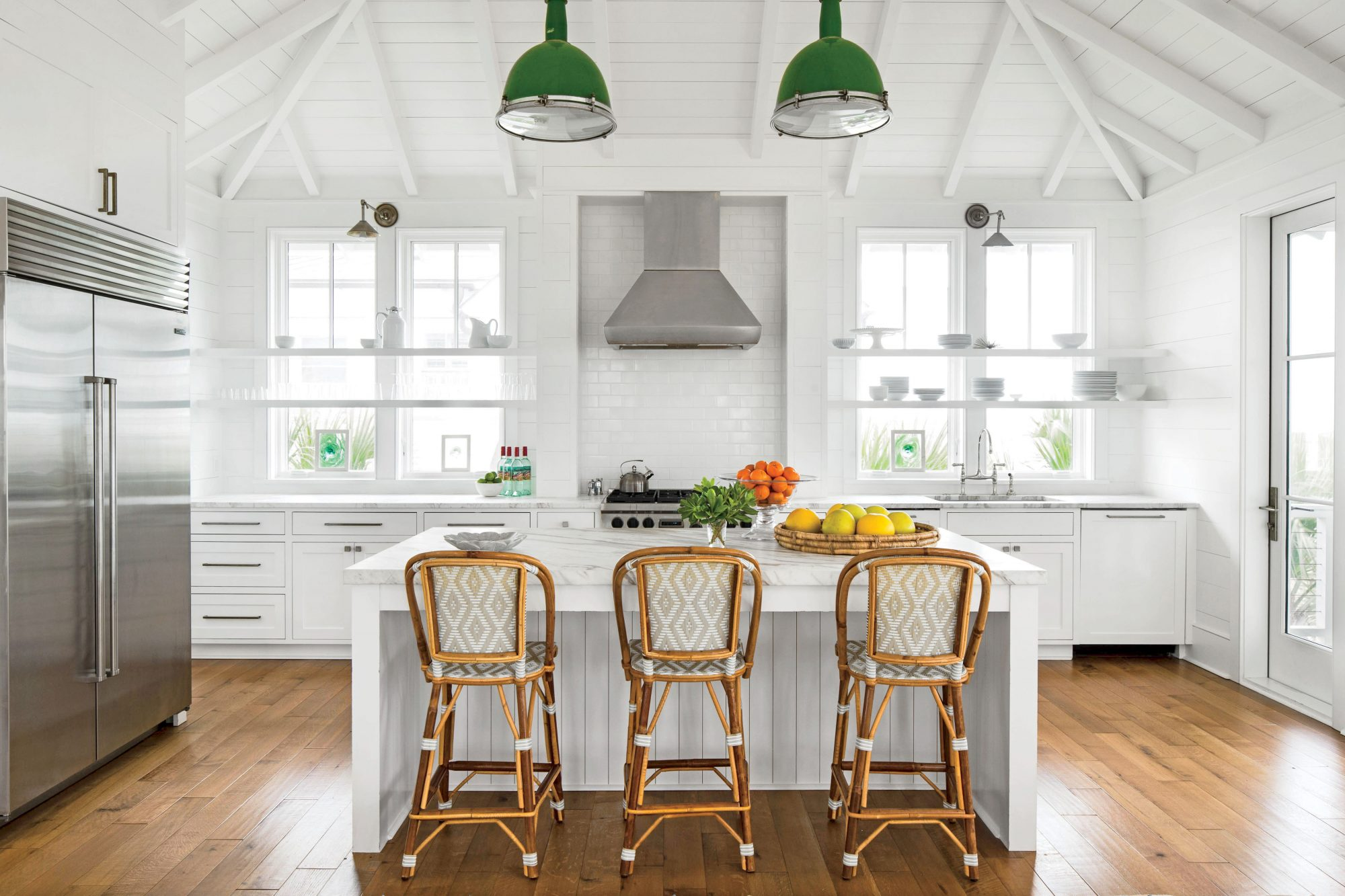 Reflecting tropical foliage just out the window, a pop of kelly green overhead via vintage gymnasium lights strung on rope gives this white kitchen a welcome dose of island color.