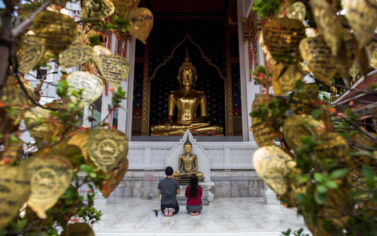 """A couple prays at the Wat Saket temple, better known as """"""""Golden Mount"""""""", in Bangkok"""