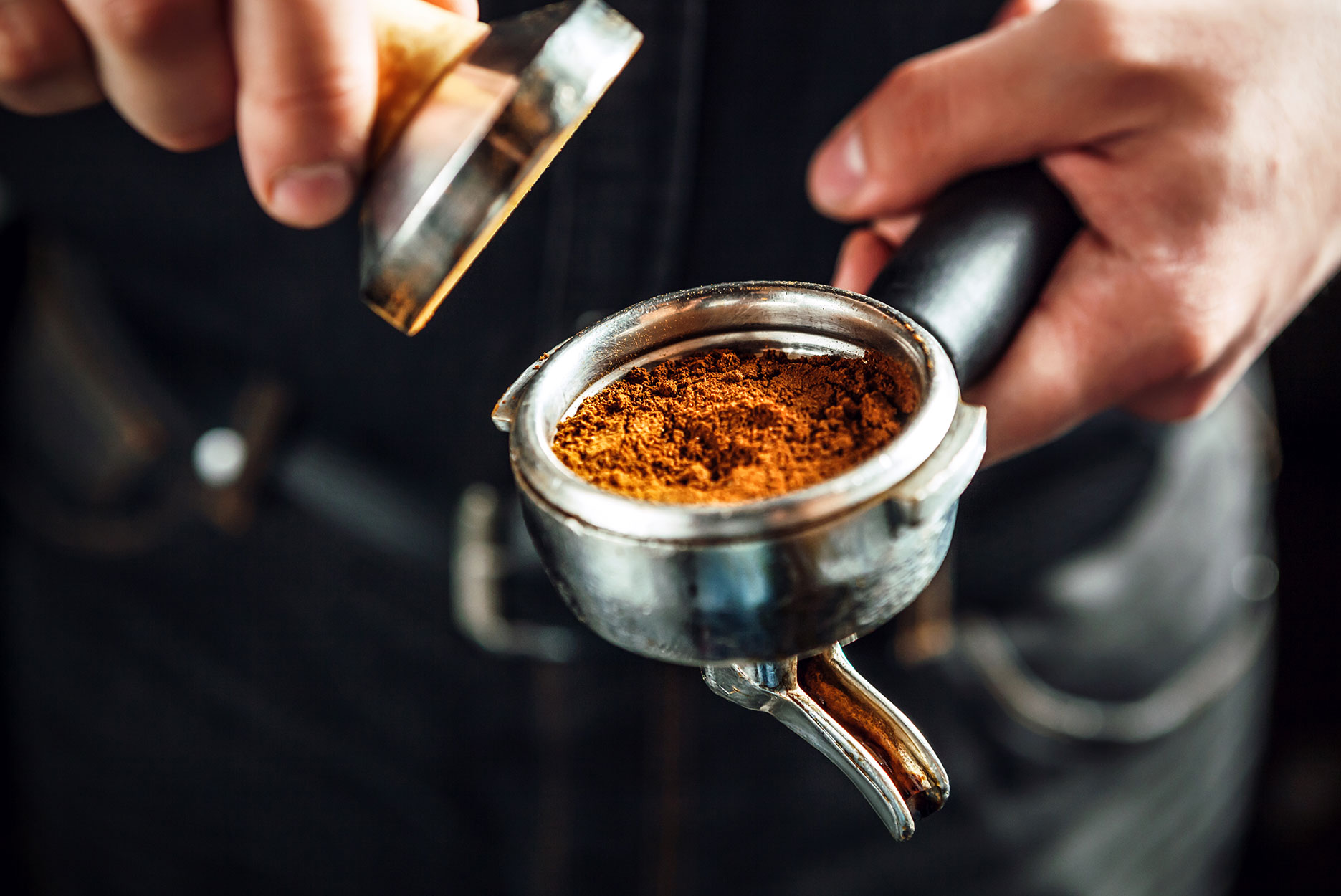 A barista preparing espresso for brewing