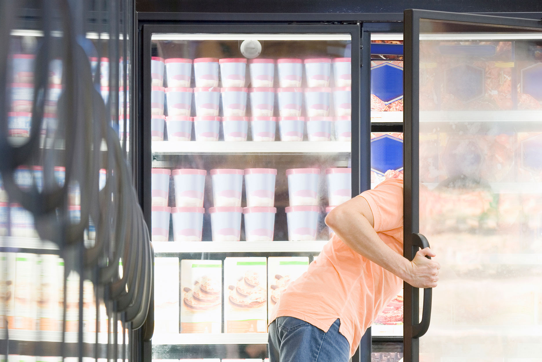 Man looking in freezer at a grocery store