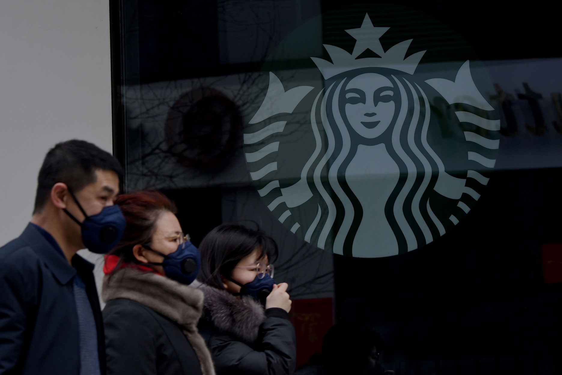 People wearing protective face masks in front of a Starbucks location in Beijing