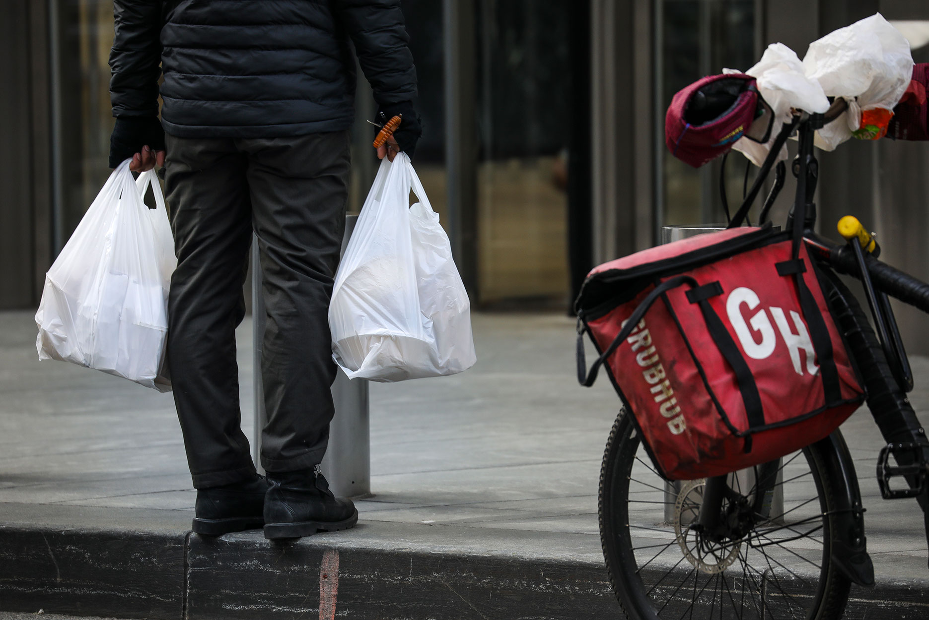 A food delivery worker carries a plastic bags in Lower Manhattan