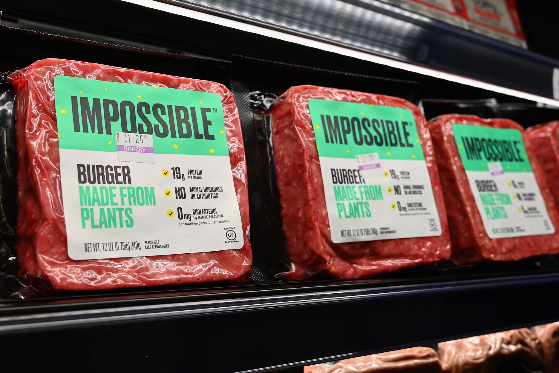 Packs of Impossible burger plant-based meat on a grocery store shelf