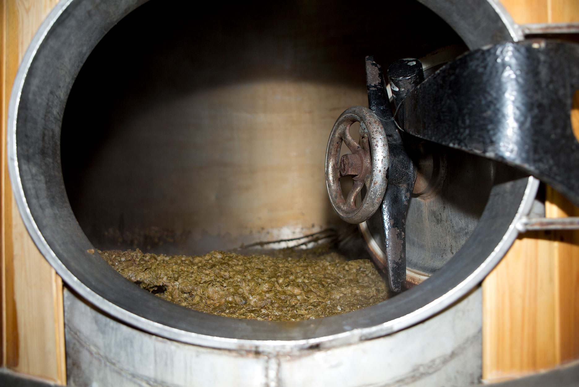 Micro brewery boiling tank with leftover millet ready to be emptied out.