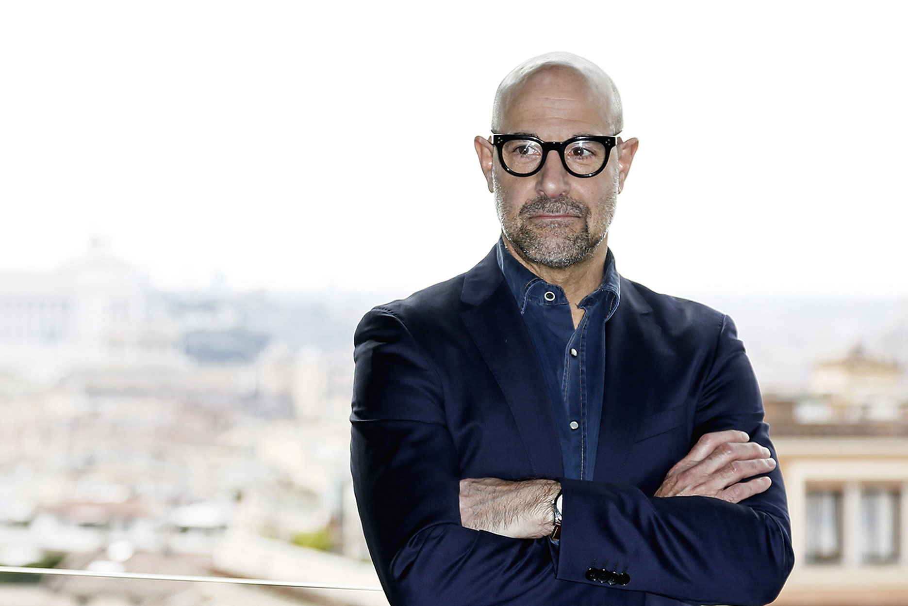 Stanley Tucci poses on a balcony in Rome