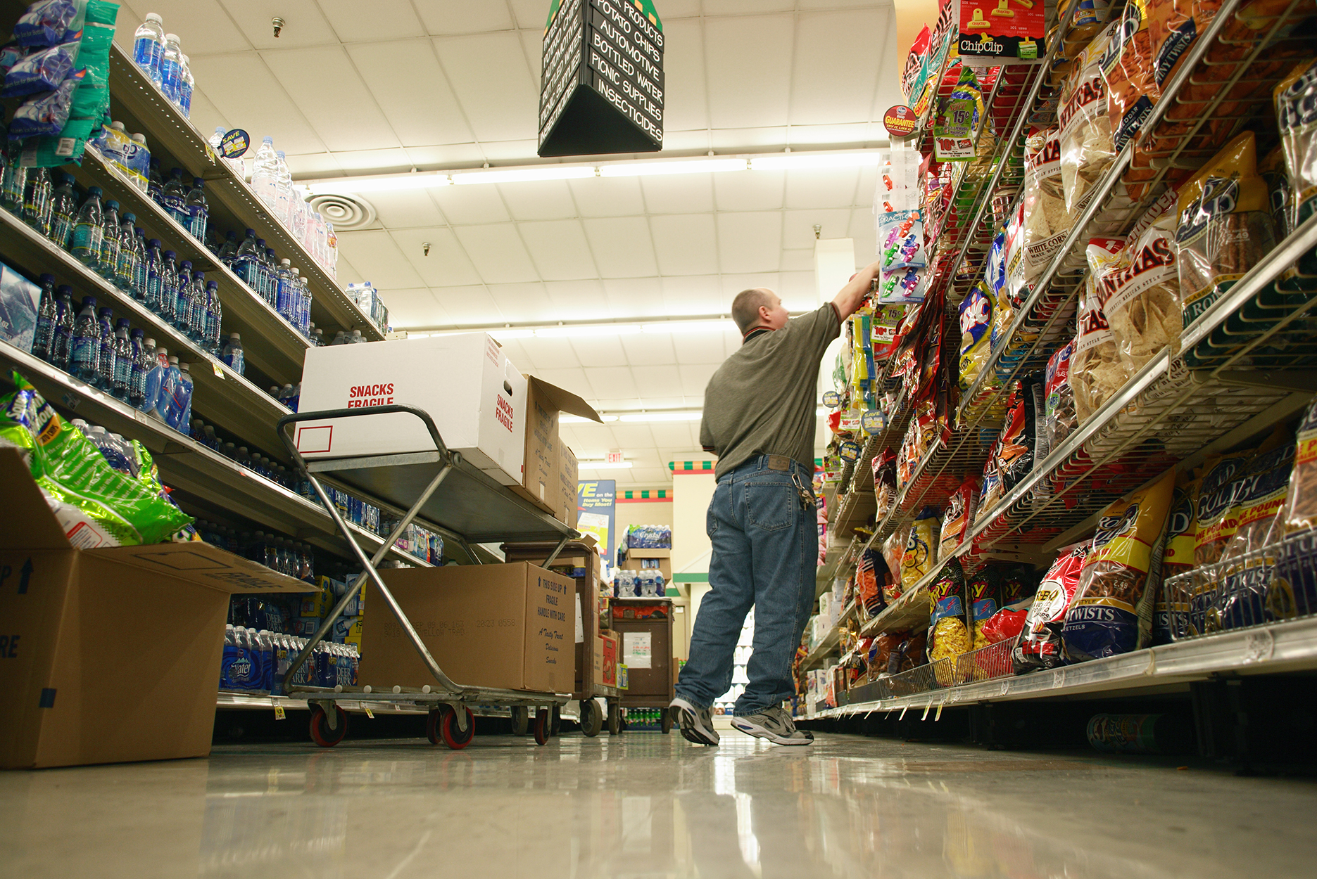 Man stocking products at grocery store, low angle view