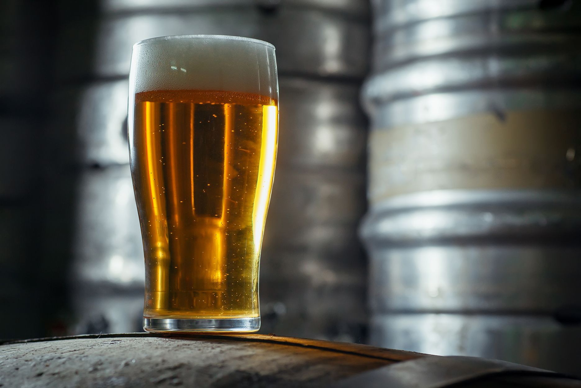 Glass full of light beer standing on top of a wooden barrel in a brewery with stainless steel kegs in the background