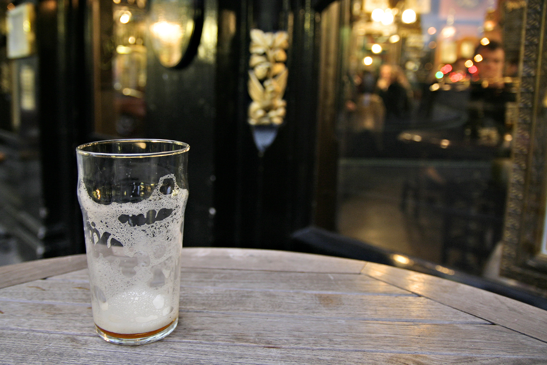 An empty beer glass outside a pub in London, England.