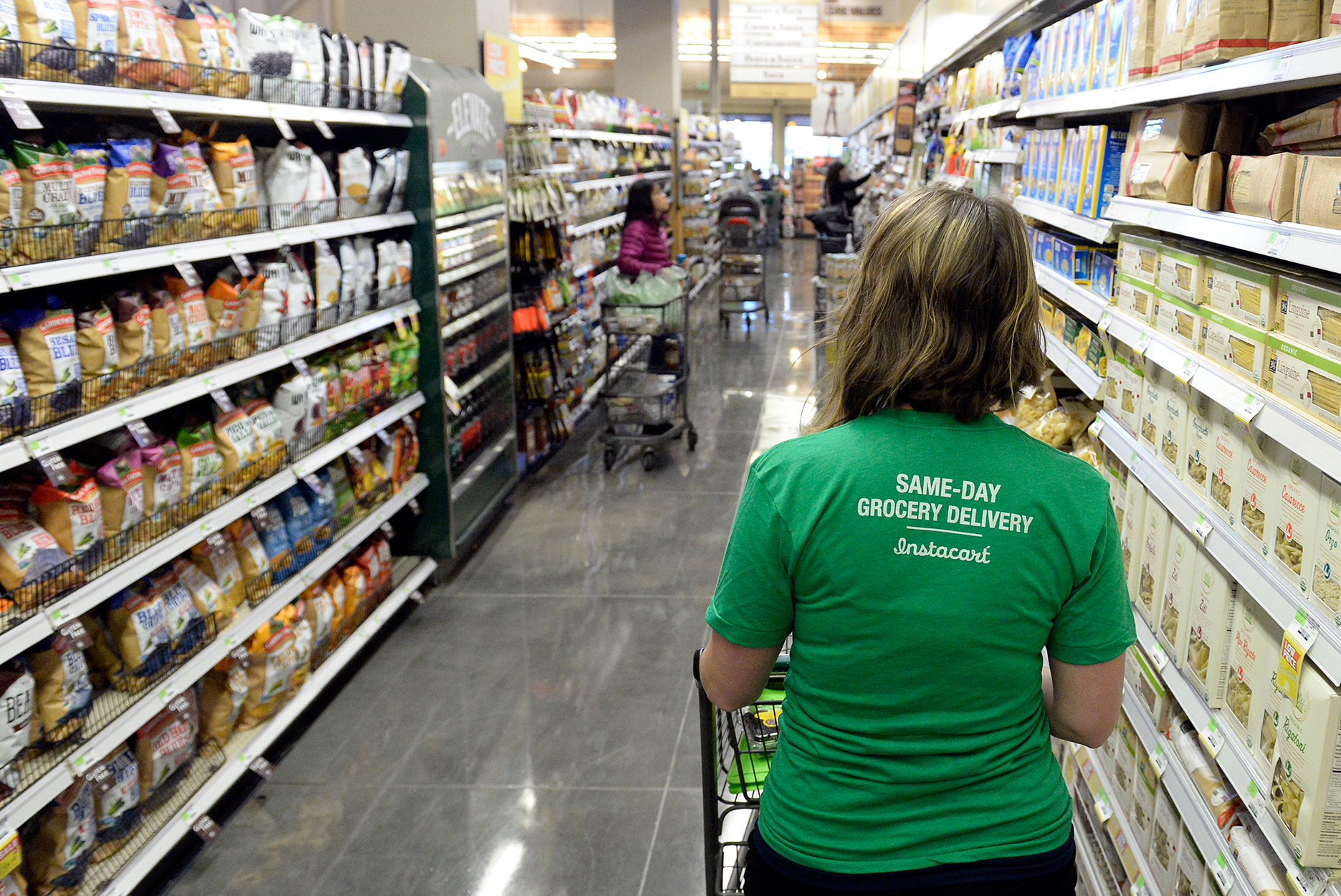 a shopper for Instacart navigates through the aisles as she shops for a customer at Whole Food in Denver, Colorado