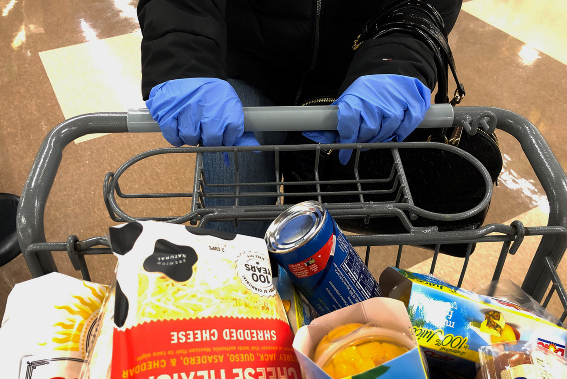 Many customers wear gloves while shopping at a supermarket in Saugus, Massachusetts on March 13, 2020. - Supermarkets and shops around Boston have been emptied by customers in fear of Covid-19.