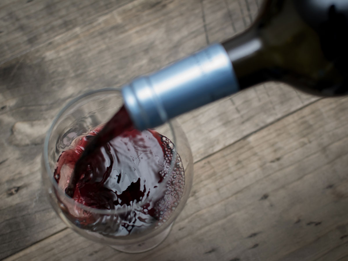 Red Wine Pouring From Bottle In Glass On Table