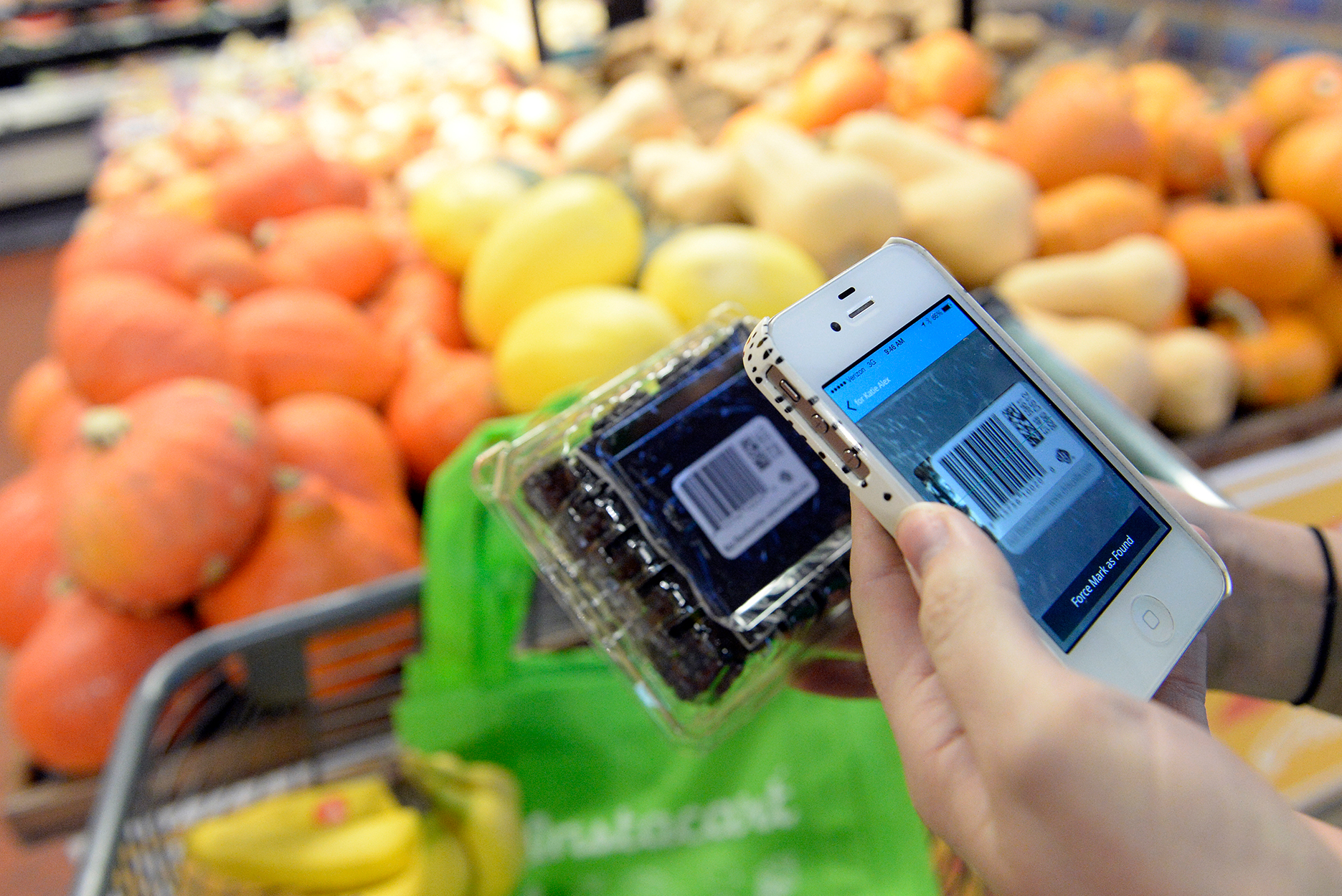 Kaitlin Myers a shopper for Instacart scans a bar code with her smart phone as she shops for a customer at Whole Foods in Denver.