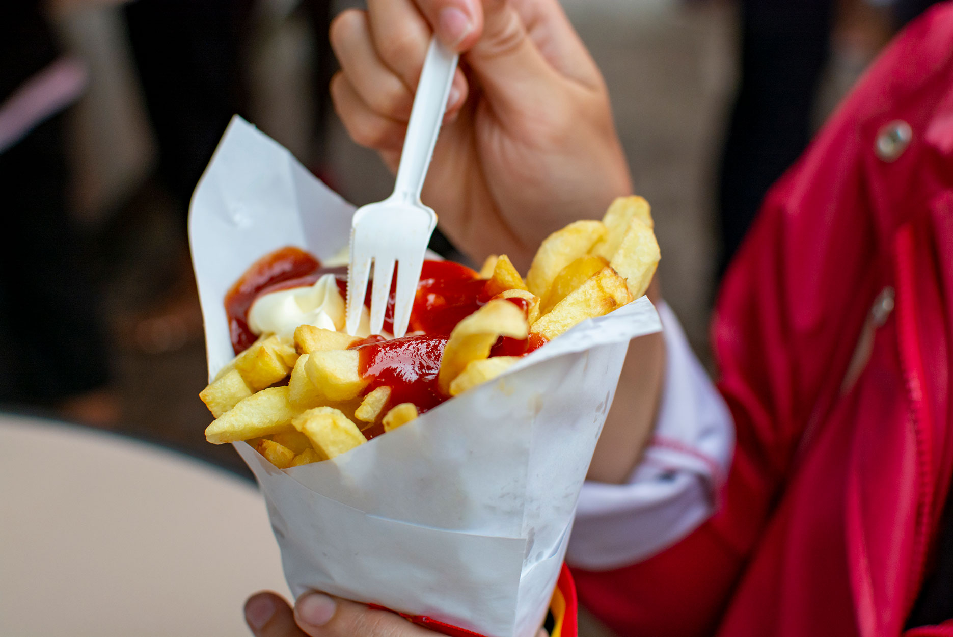 Eating of Belgian fried potatos chips with ketchup and mayonnaise, street fast food