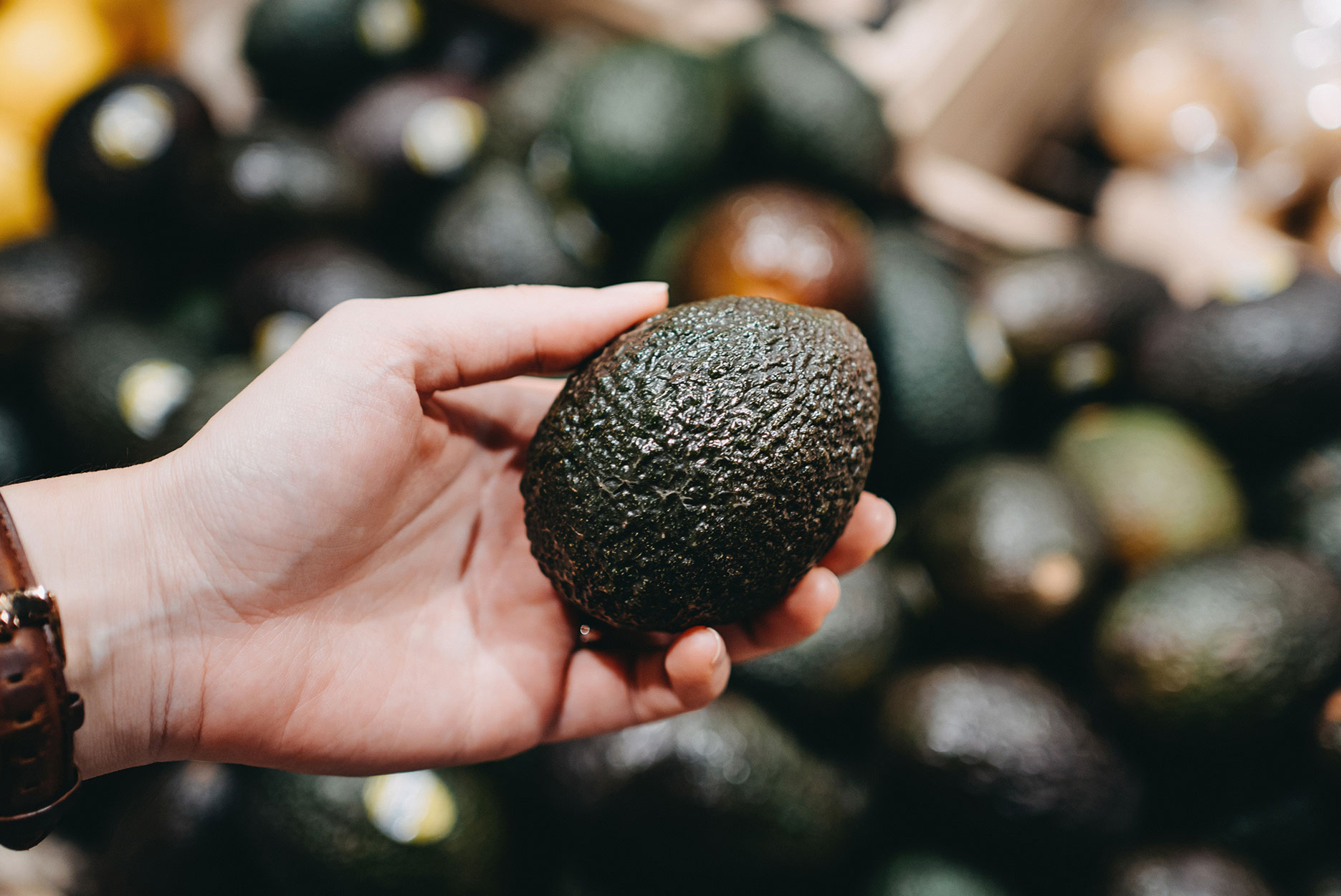 Woman shopping for fresh fruit and vegetables in supermarket, close up of her hand choosing avocados