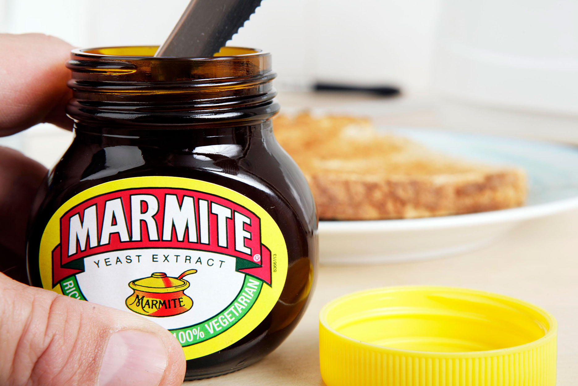 A man getting Marmite out of the jar with a knife.