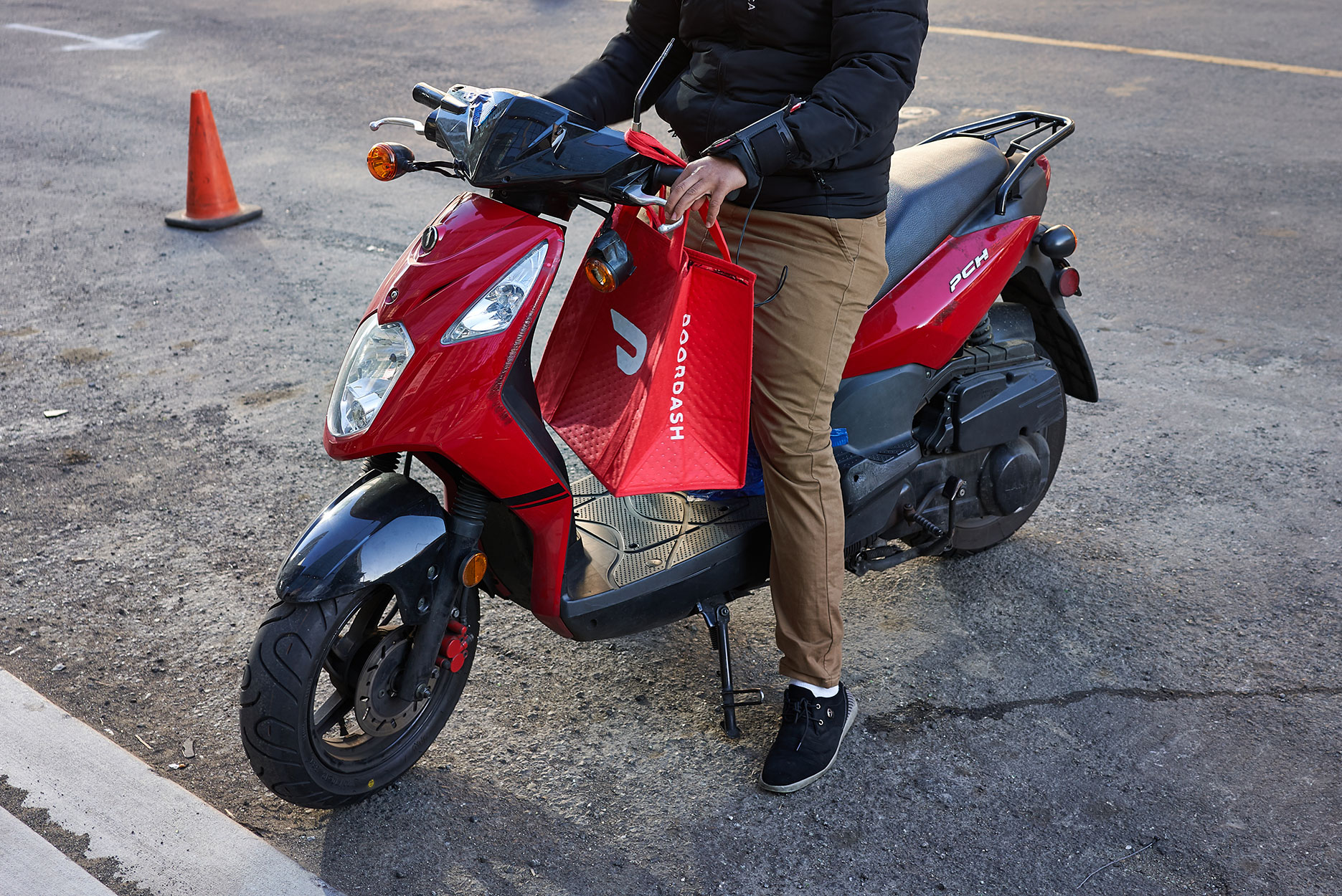 A DoorDash delivery worker on his motorcycle in the SoMa neighborhood of San Francisco, California.