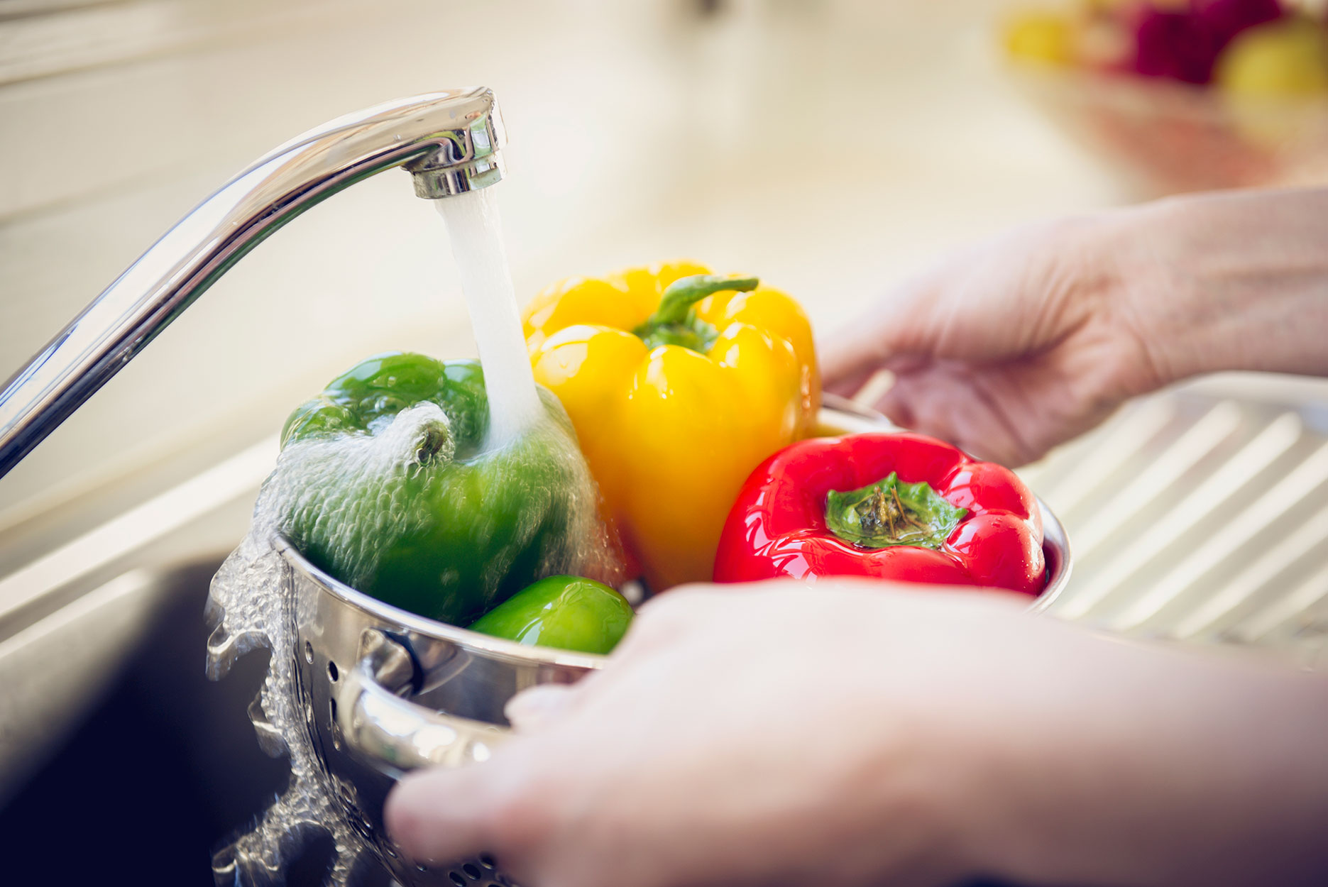 Hands of Hispanic woman rinsing peppers in sink