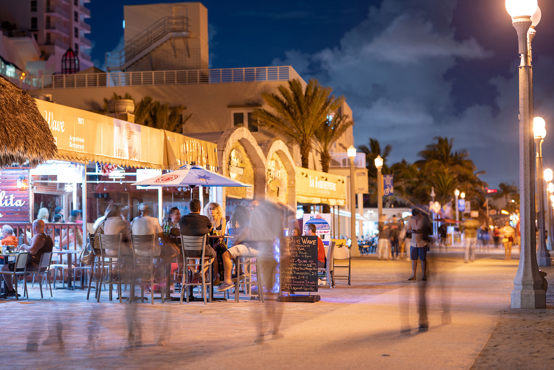 Tourism on Hollywood Beach FL night photo tourists sitting on tables eating and drinking