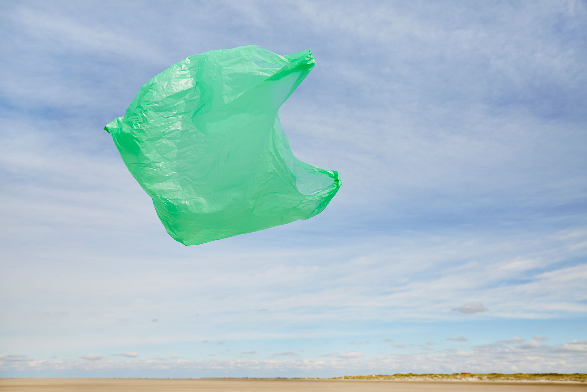 Plastic bag flying in the wind on the beach against sky