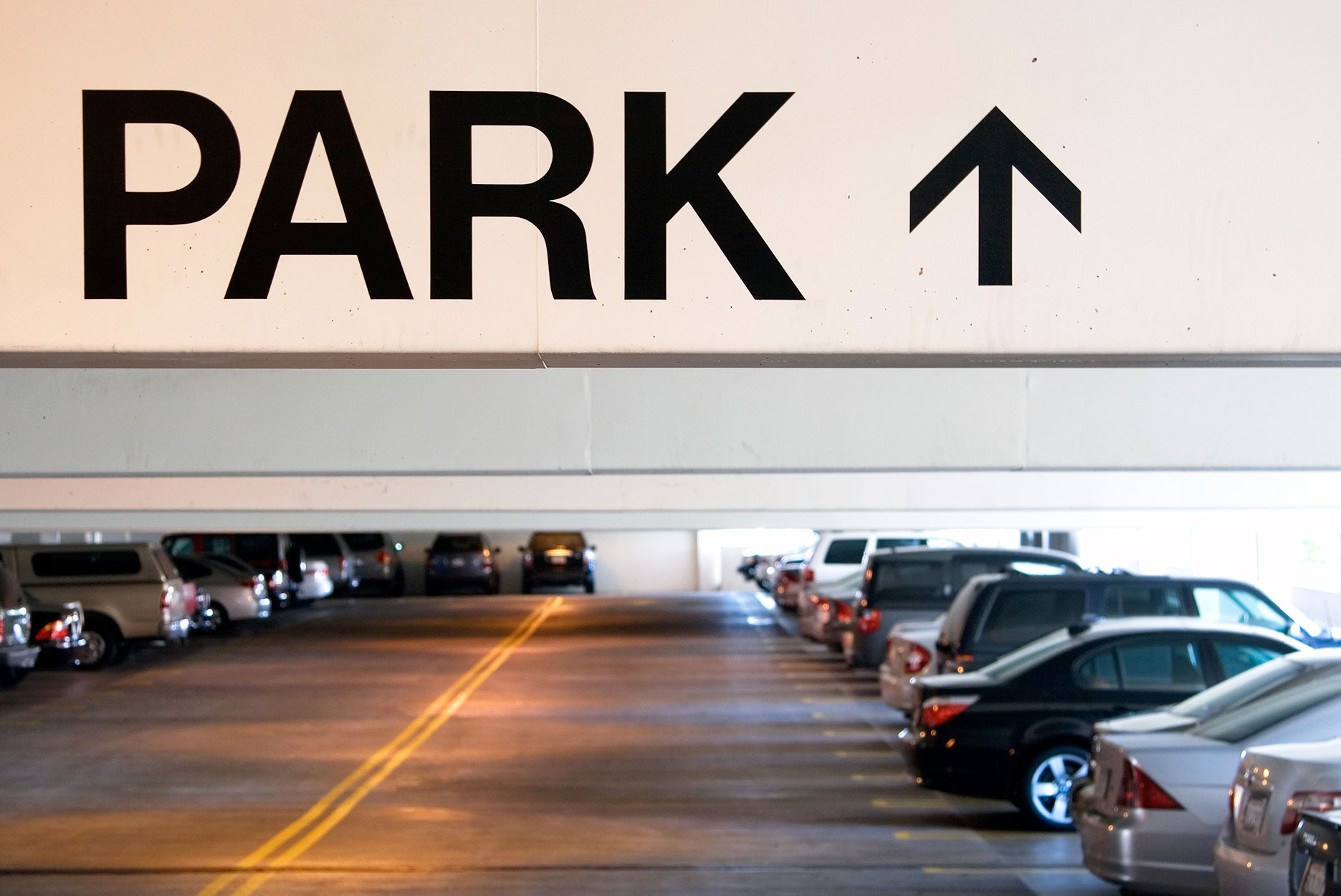 Sign indicating parking lot on top of parking with cars