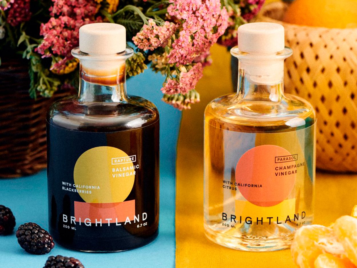 Brightland Balsamic and Champagne Vinegars on a colorful tablecloth