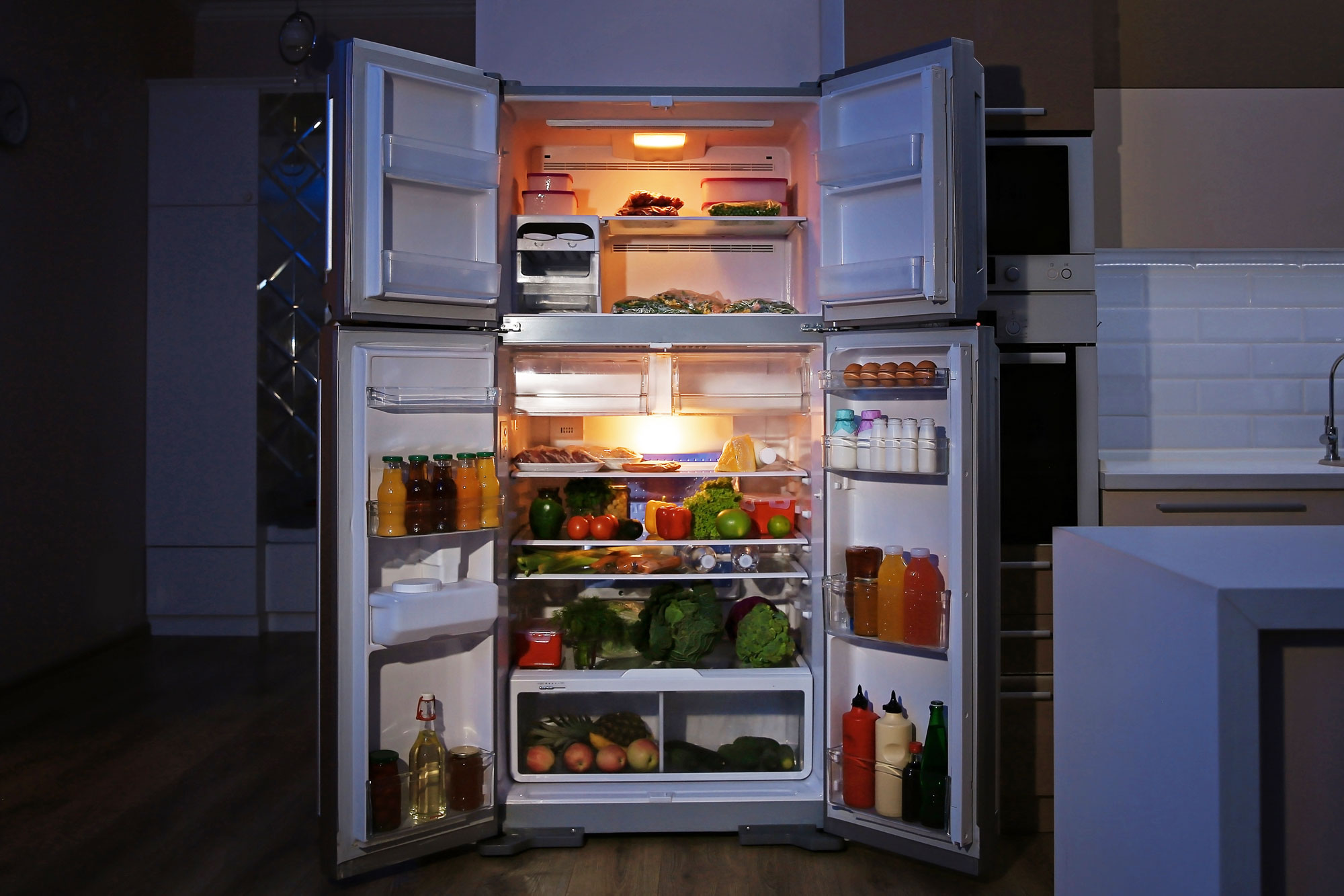 Fully Stocked Refrigerator Open in a dark kitchen
