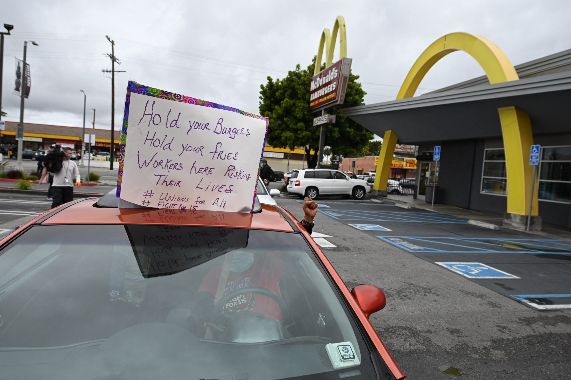 McDonald's employees and supporters protest outside a McDonald's in Los Angeles, California, April 6, 2020 demanding pay for quarantine time and healthcare for workers who get sick from the coronavirus that causes COVID-19.