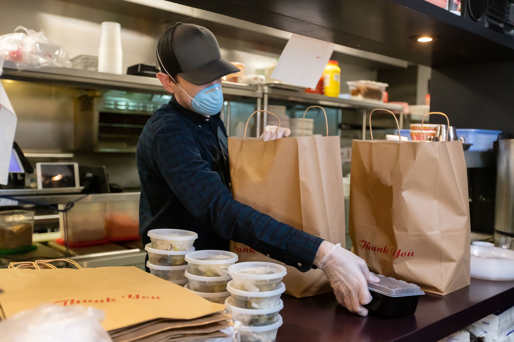 Gloved and Masked man in Restaurant Kitchen Preparing Food for Delivery During Covid-19 Pandemic