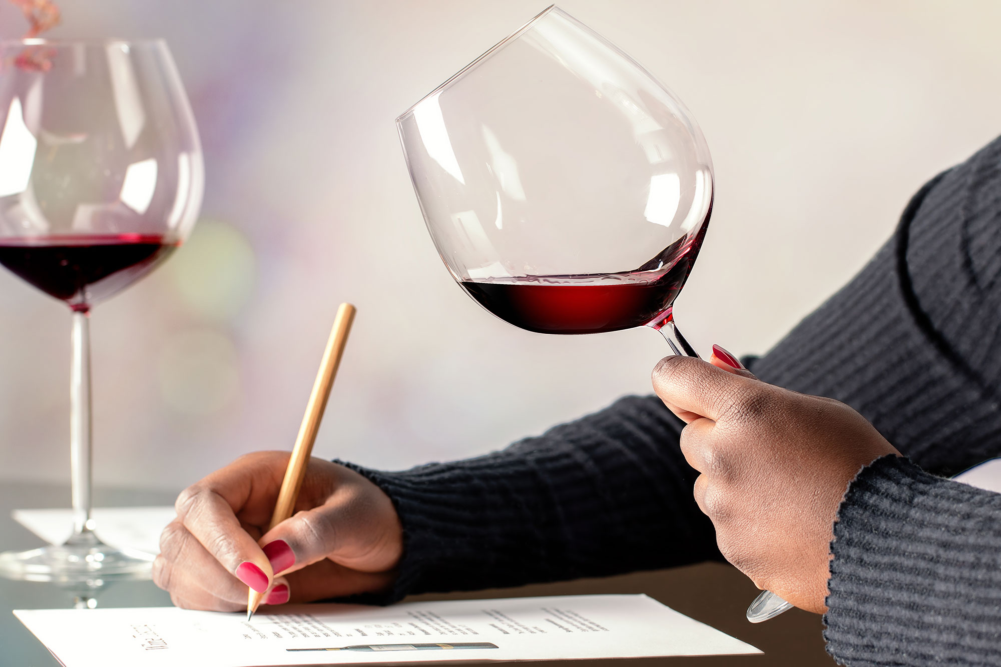 African female sommelier evaluating red wine at table.