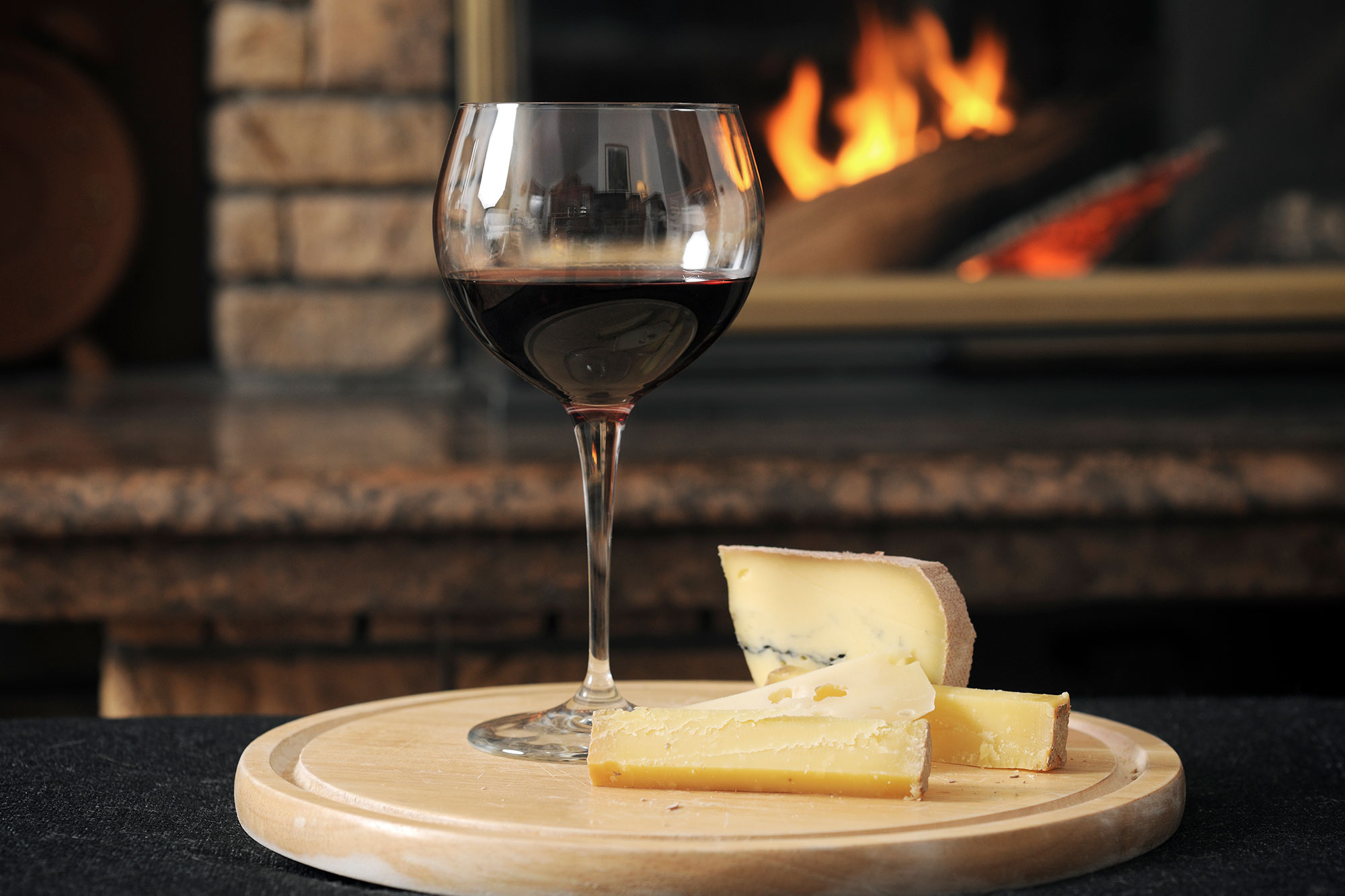 Close-up of wine with cheese slices served on wooden tray against fireplace