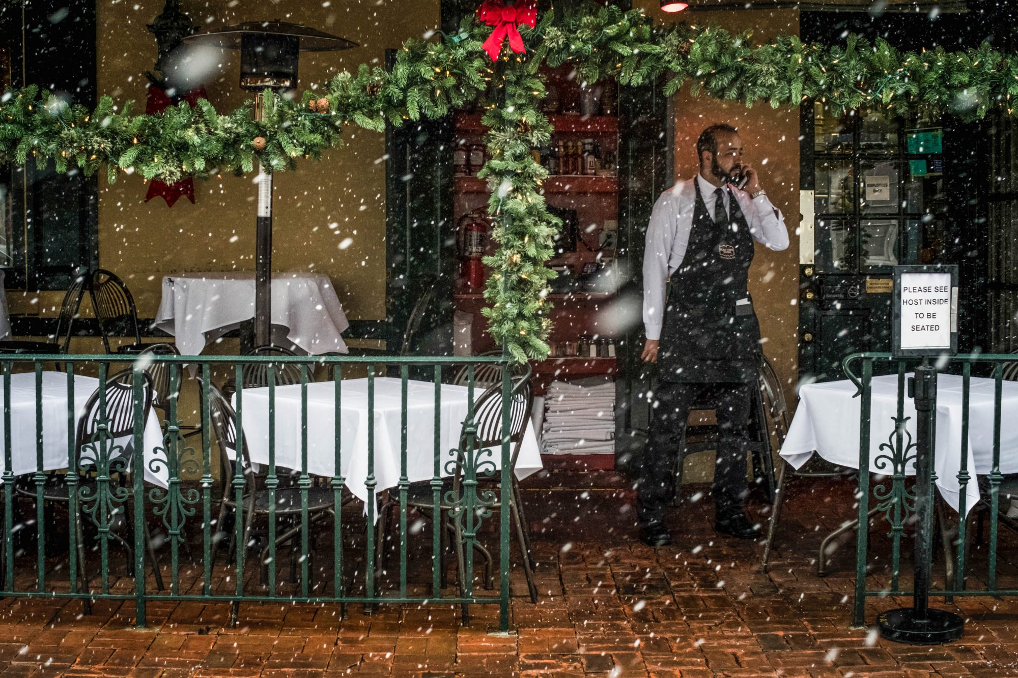 Waiter stands outside of restaurant as it snows