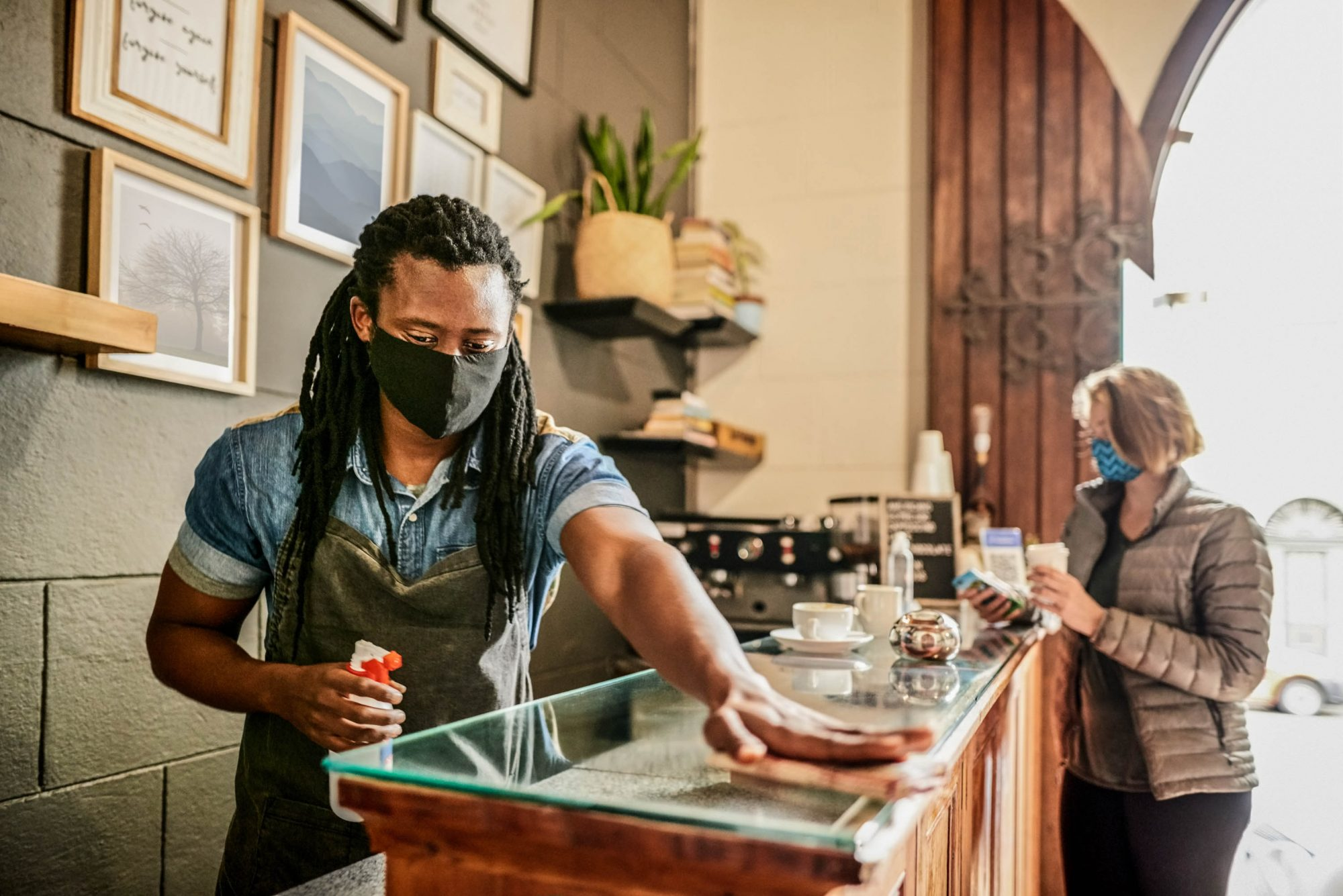 Barista wearing protective face mask cleaning and disinfecting cafe counter with a customer sitting at back