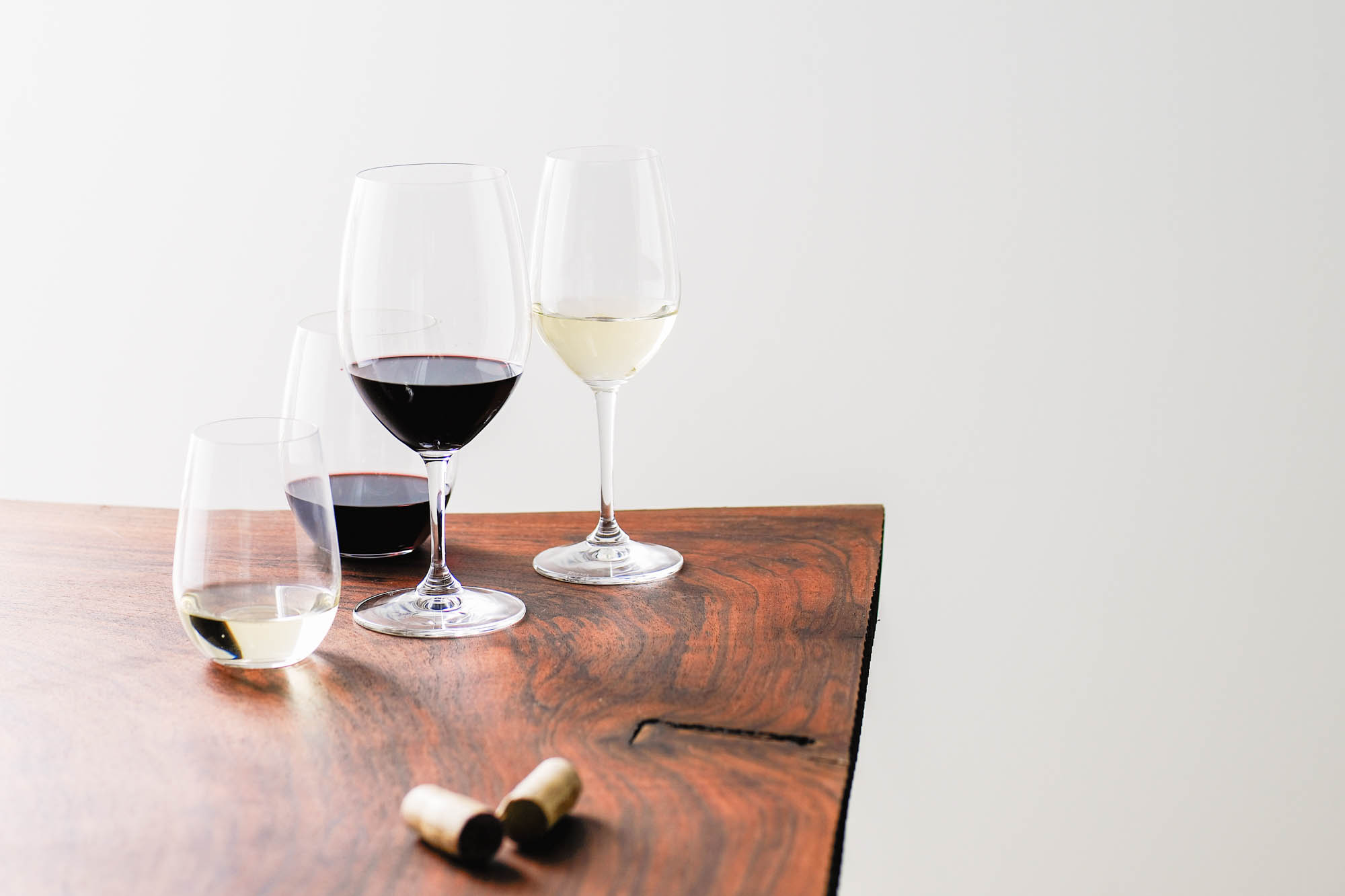 Glasses of red and white wine sitting on table