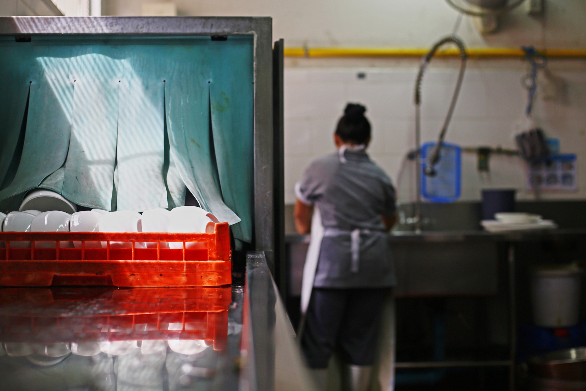 Restaurant worker washing dishes in a commercial kitchen