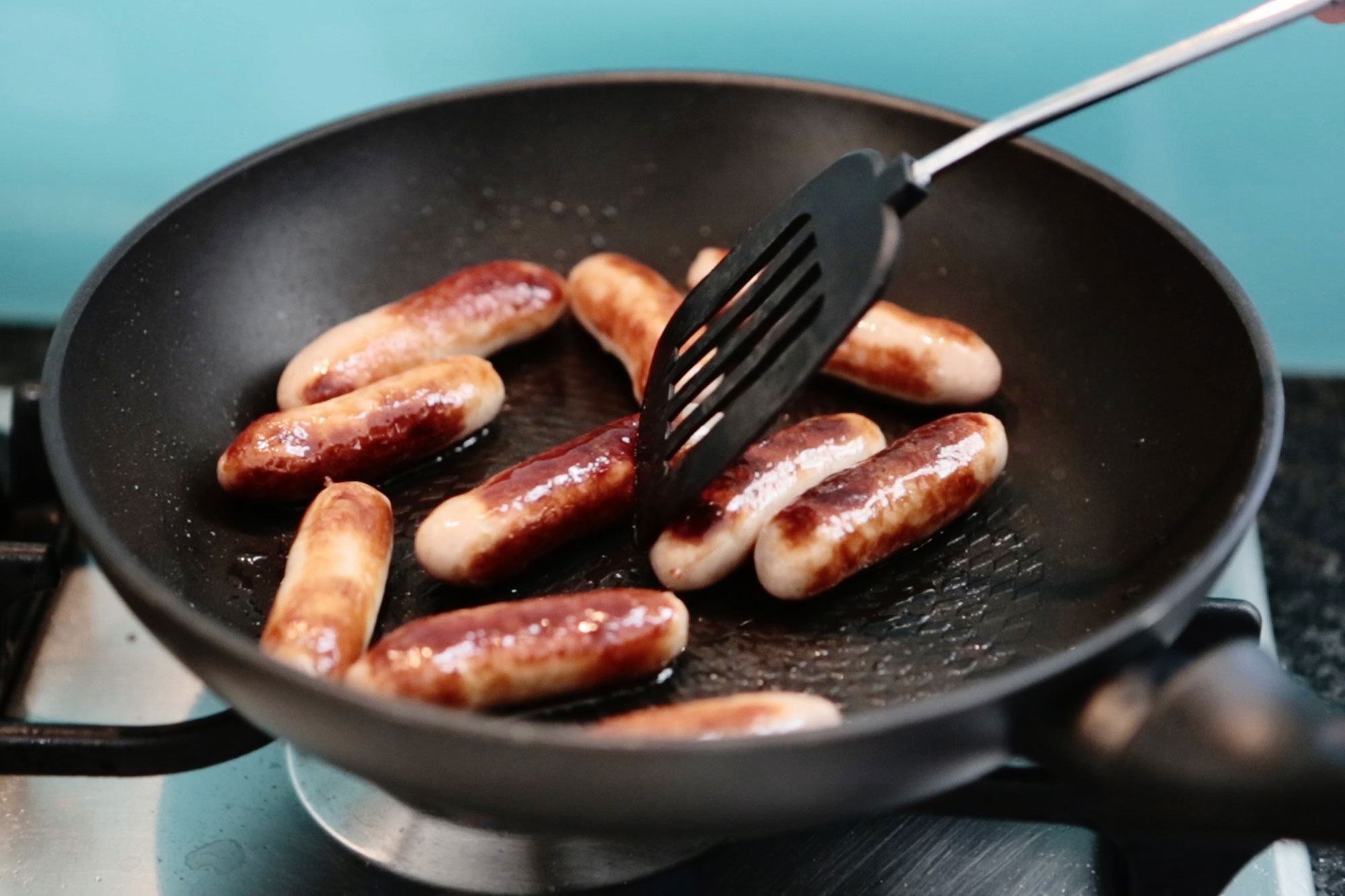 Sausages sizzling in non-stick pan while being stirred