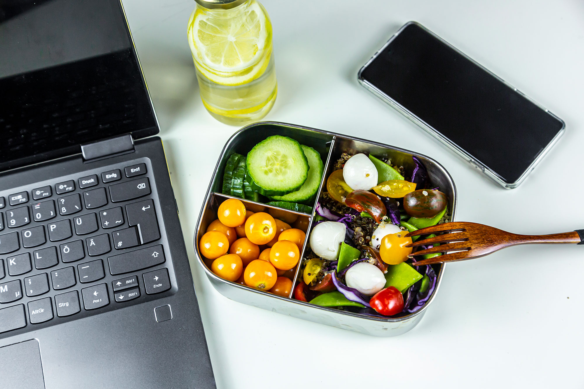 Laptop, smart phone, bottle of lemonade and lunchbox with cucumber slices, winter cherries and quinoa salad (quinoa, cherry tomato, red cabbage, sugar snap peas and mozzarella balls)