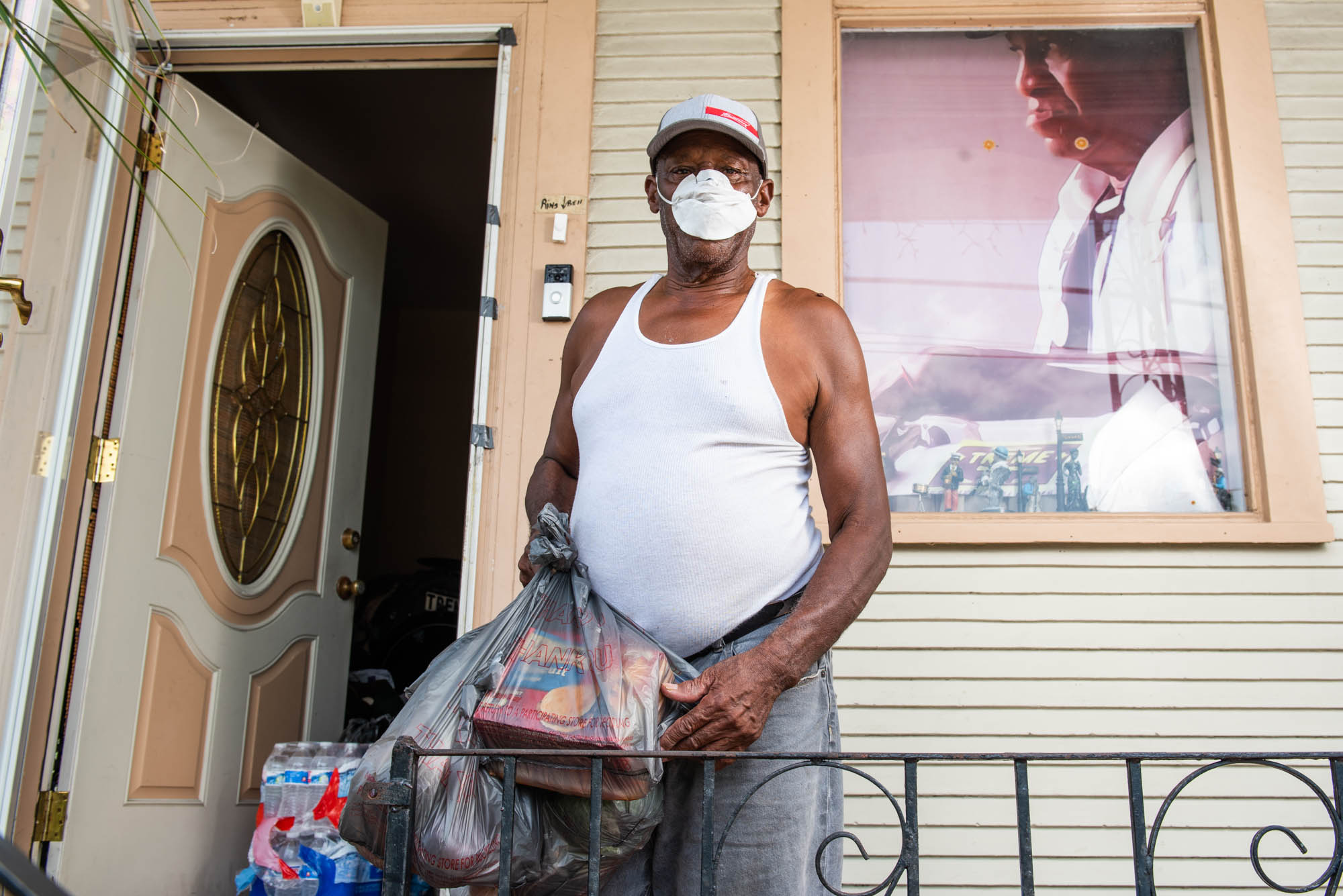 Benny Jones, band leader of the Treme Brass Band, gets a home delivery of groceries from Feed the Second Line volunteer and Red Bean Krewe member Julie