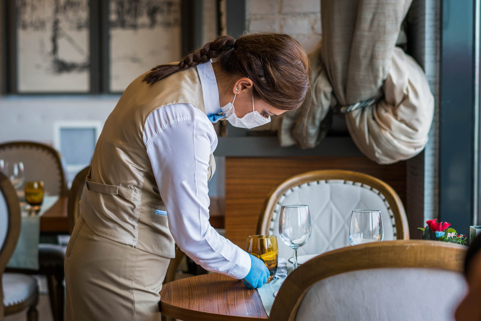 Waitress with a mask disinfects the table