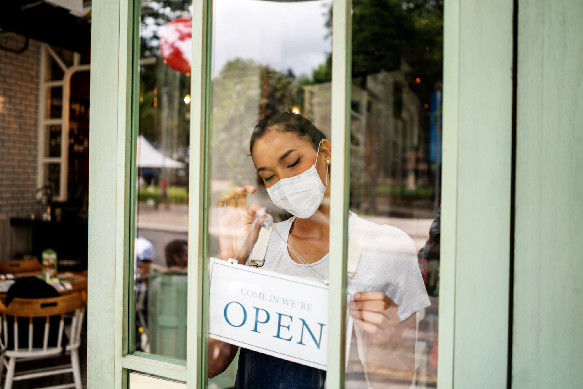 Restaurant employee hanging open sign, wearing a mask