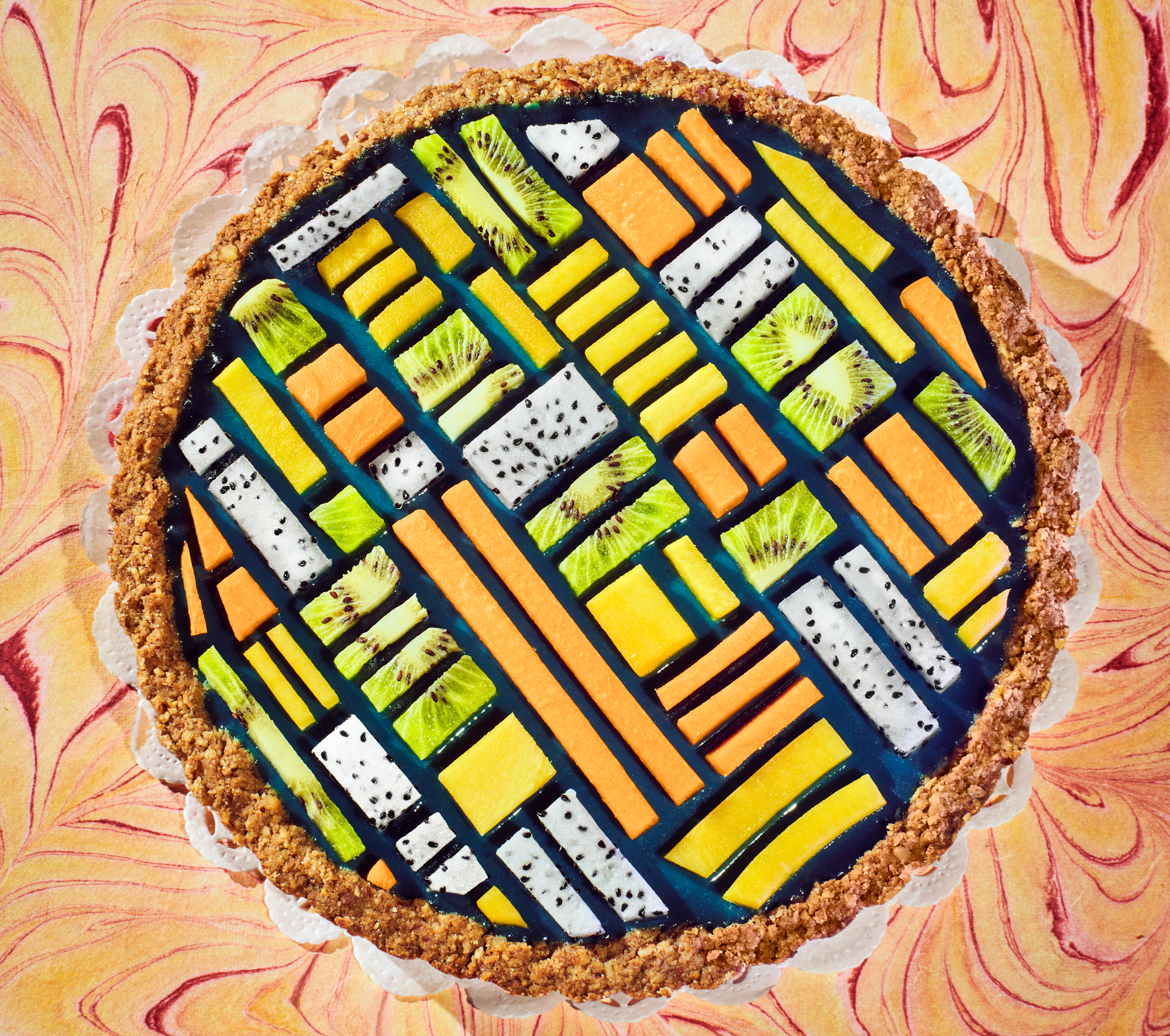 Pie with pattern of papaya, mango, and kiwi slices