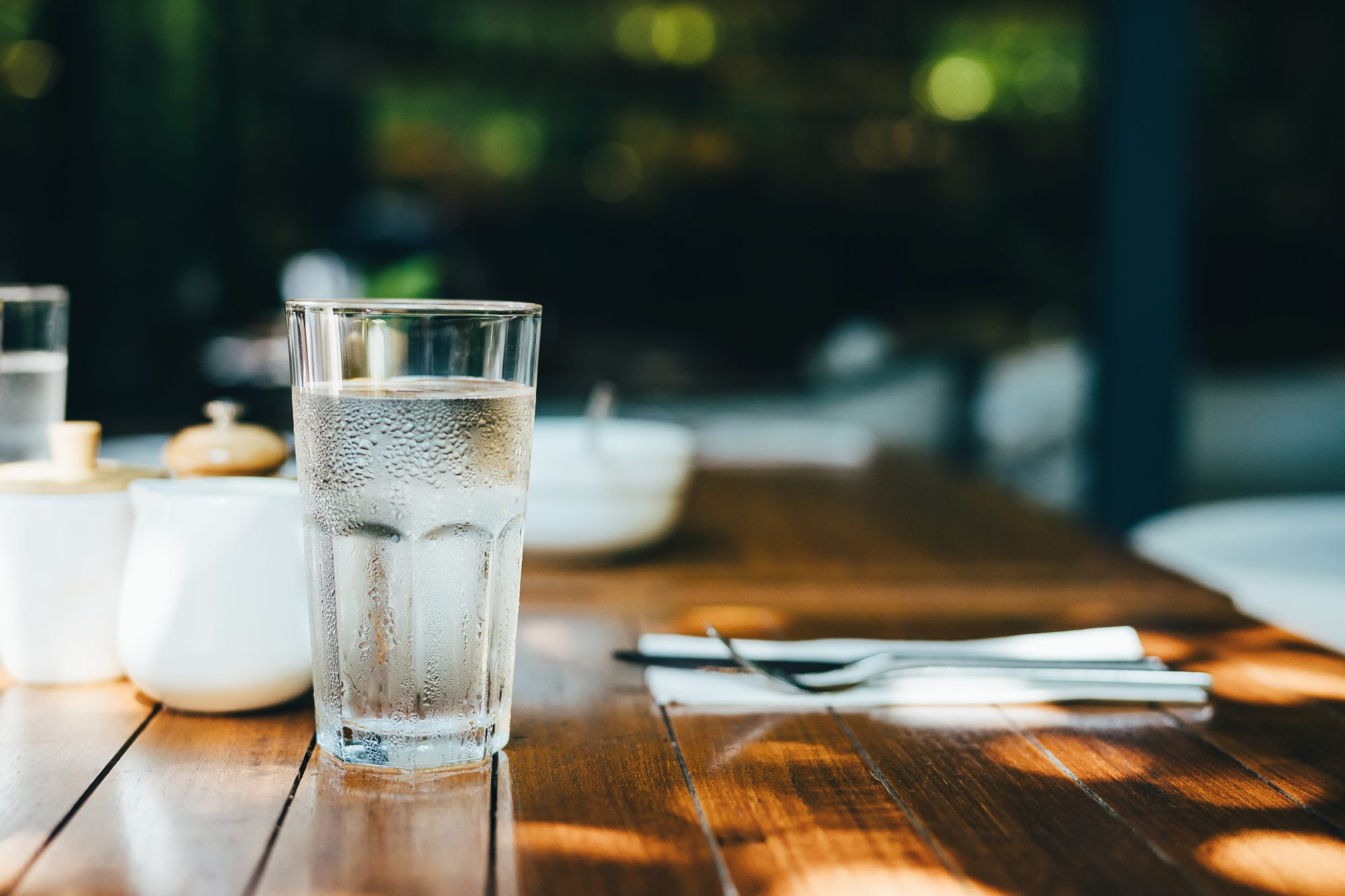 A glass of water served on table in an outdoor restaurant against beautiful sunlight