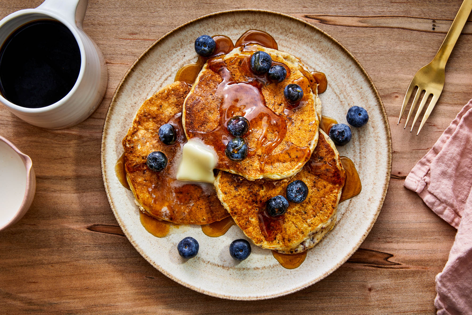 Breakfast scene with quinoa pancakes, blueberries, syrup