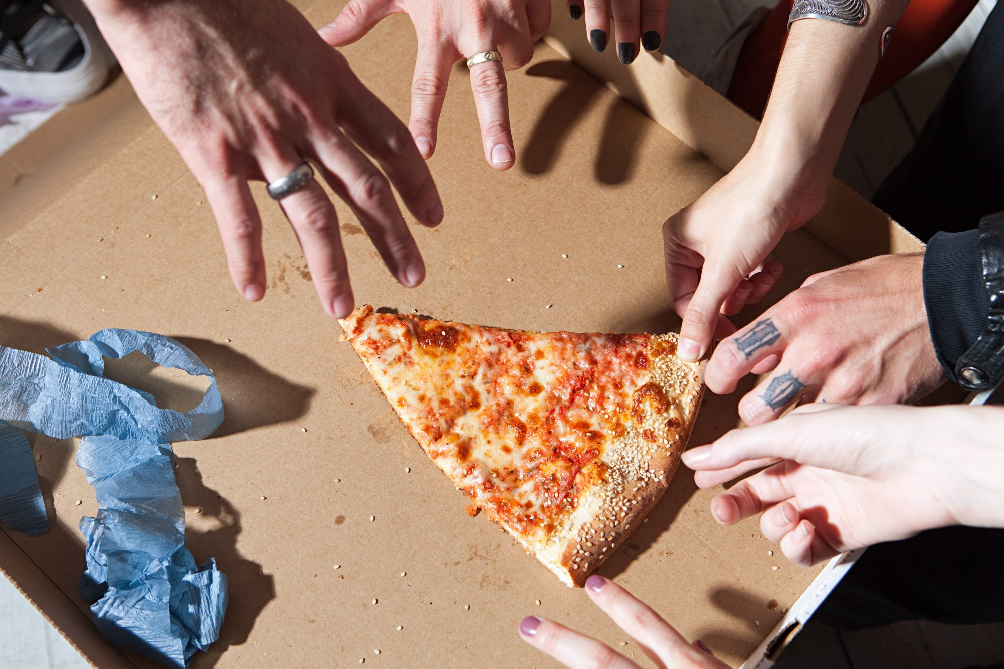 People taking slice of pizza at party