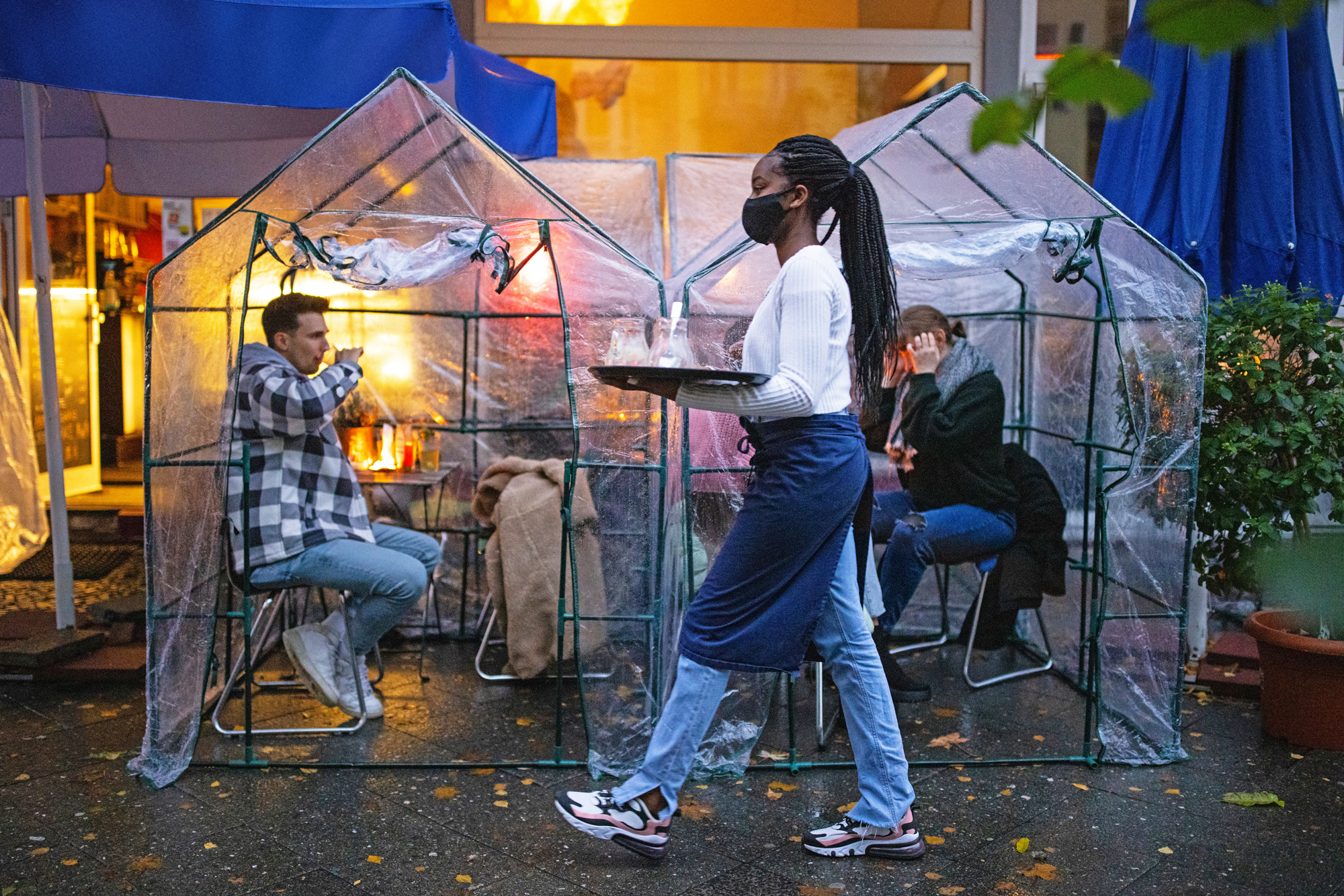 People sitting inside plastic tents at outdoors cafe with restaurant server wearing face mask carrying a serving tray.