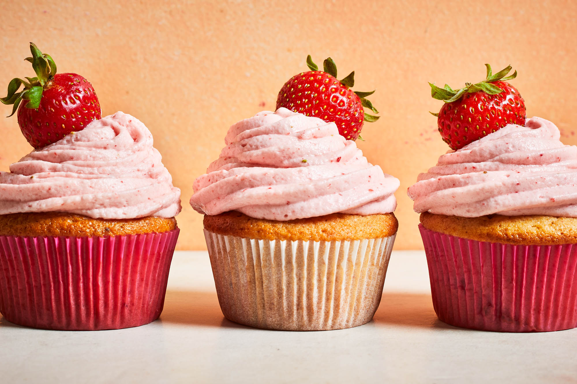 three strawberry cupcakes with cream cheese frosting