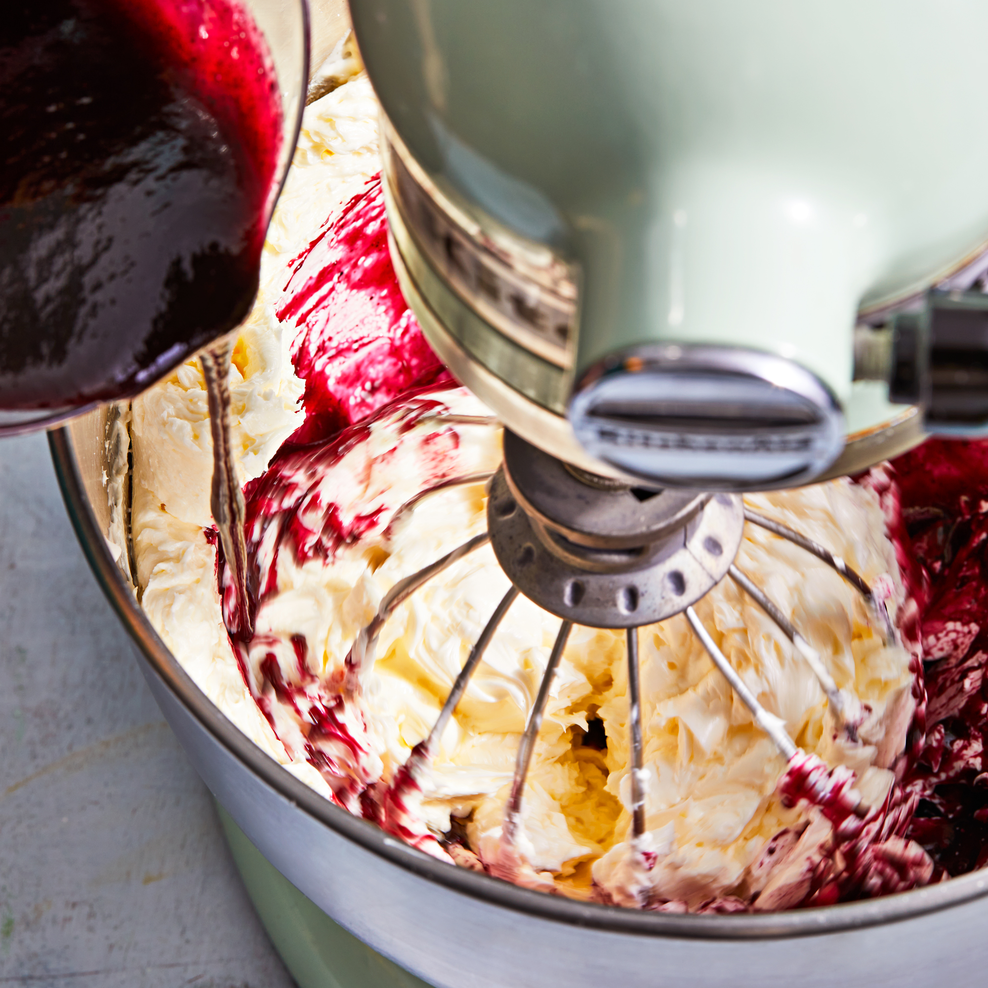 pouring jam into mixer with buttercream frosting