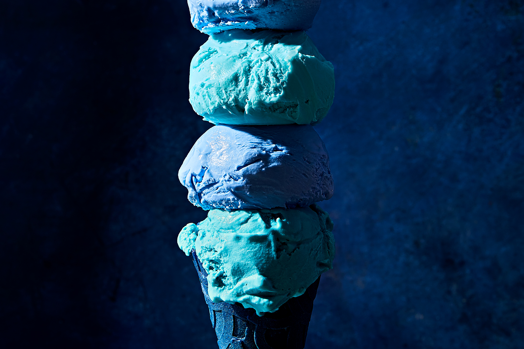 blue cone with many scoops of blue moon ice cream