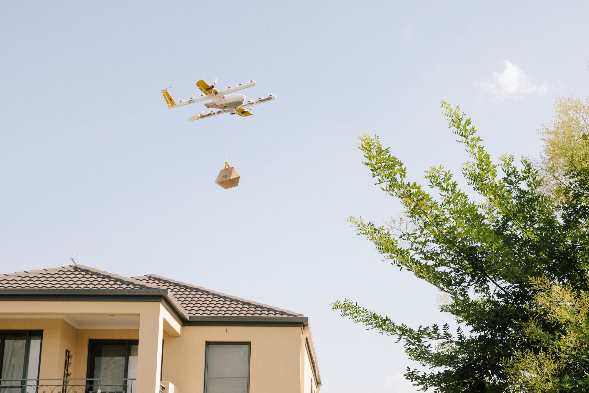 A Wing drone delivering a package