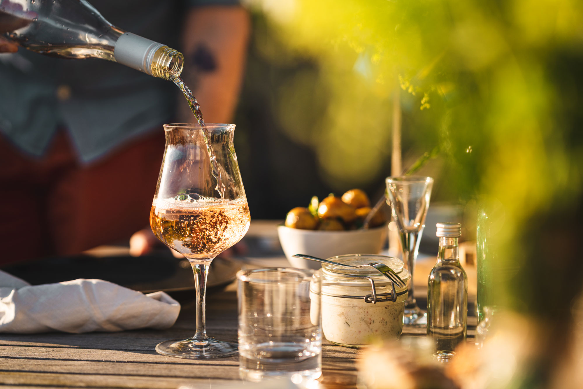 Man pouring up rose wine outdoors