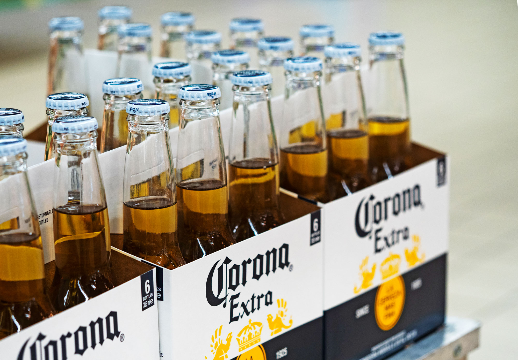 Bottles of Corona Extra beer are on a shelf in a store.